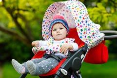 Bebê bonito pequeno bonito de 6 meses que sentam-se na mamã do pram ou do carrinho de criança e da espera Fotos de Stock Royalty Free