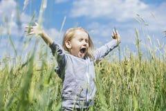 Bebê bonito pequeno fora em um campo no ar fresco Imagem de Stock Royalty Free