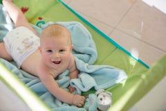 Bebê bonito pequeno, jogando com brinquedos em uma ucha móvel em uma SU fotos de stock