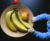 Bebê bonito pequeno que realiza na placa de madeira original das mãos com maçãs e bananas Material orgânico da bacia com linhas c imagem de stock royalty free