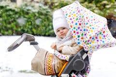 Bebê bonito pequeno bonito que senta-se no pram ou no carrinho de criança no dia frio com granizo, chuva e neve Fotos de Stock Royalty Free
