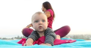 Bebê bonito perto da mãe que faz a ioga filme