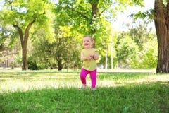 Bebê bonito que aprende andar no parque fotografia de stock royalty free