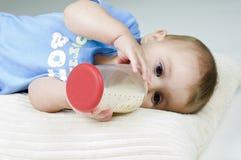 Bebê bonito que bebe do frasco Fotografia de Stock Royalty Free