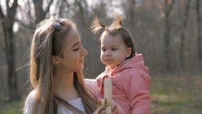 Bebê bonito que come a banana nos braços da mãe filme