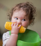 Bebê bonito que come o milho fotos de stock