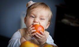 Bebê bonito que come uma maçã vermelha suculenta fotos de stock royalty free