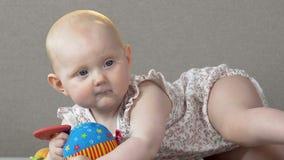 Bebê bonito que encontra-se na barriga no sofá, tentando morder o brinquedo de borracha, berçário video estoque