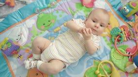 Bebê bonito que encontra-se na parte traseira Bebê infantil feliz que olha a câmera Tempo bonito da criança filme