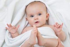 Bebê bonito que encontra-se na toalha branca Foto de Stock Royalty Free