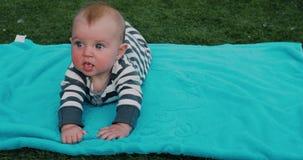 Bebê bonito que encontra-se na toalha no gramado filme