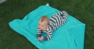 Bebê bonito que encontra-se na toalha no gramado vídeos de arquivo