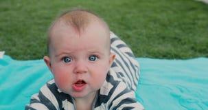 Bebê bonito que encontra-se na toalha no gramado video estoque