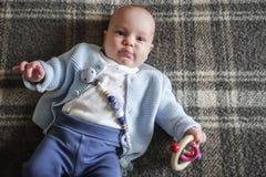 Bebê bonito que encontra-se no seu para trás Fotos de Stock