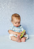 Bebê bonito que estuda o assento do livro Imagens de Stock