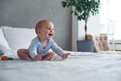 Bebê bonito que joga com o brinquedo feito malha na cama em casa imagem de stock royalty free
