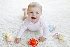 Bebê bonito que joga com o brinquedo pastel colorido do chocalho do vintage Imagem de Stock Royalty Free