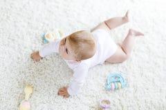 Bebê bonito que joga com o brinquedo pastel colorido do chocalho do vintage Fotos de Stock
