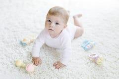 Bebê bonito que joga com o brinquedo pastel colorido do chocalho do vintage Foto de Stock