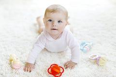 Bebê bonito que joga com o brinquedo pastel colorido do chocalho do vintage Fotografia de Stock