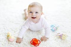 Bebê bonito que joga com o brinquedo pastel colorido do chocalho do vintage Fotografia de Stock Royalty Free