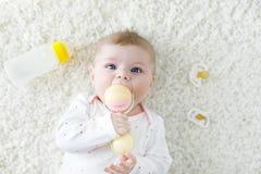 Bebê bonito que joga com o brinquedo pastel colorido do chocalho do vintage Imagens de Stock