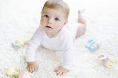 Bebê bonito que joga com o brinquedo pastel colorido do chocalho do vintage Fotos de Stock Royalty Free