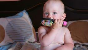 Bebê bonito que joga com o pente na cama Sorrisos e tentativas para pentear-se Criança 1 ano No pente é um espelho video estoque