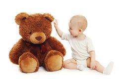 Bebê bonito que joga com o urso de peluche grande no branco Fotos de Stock