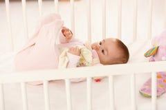 Bebê bonito que joga com pés Imagens de Stock Royalty Free