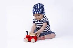 Bebê bonito que joga com pouco trem Fotos de Stock Royalty Free