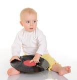 Bebê bonito que joga com registro de vinil velho no fundo branco Foto de Stock