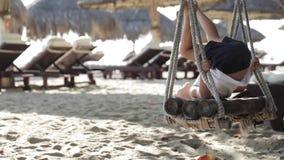 Bebê bonito que joga e que faz o exercício ginástico no balanço no Sandy Beach filme