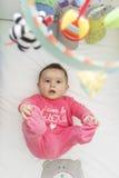Bebê bonito que ri e que olha acima a seus brinquedos em sua ucha Imagens de Stock Royalty Free