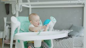 Bebê bonito que senta-se no cadeirão que lambe a placa filme