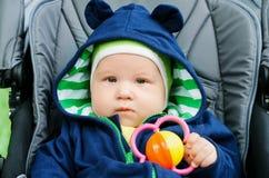 Bebê bonito que senta-se no carrinho de criança Imagem de Stock