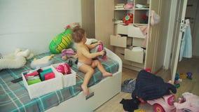 Bebê bonito que tenta em chapéus do inverno no quarto desarrumado video estoque