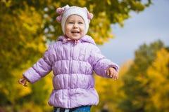 Bebê brincalhão feliz no parque do outono Foto de Stock Royalty Free