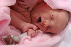 Bebê carregado com a colher de prata em sua boca Foto de Stock Royalty Free