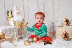 Bebê caucasiano com olhos azuis no traje do duende que comemora o feriado do Natal ou do ano novo Imagem de Stock