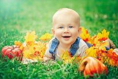 Bebê caucasiano de sorriso adorável com olhos azuis no t-shirt e no romper das calças de brim que encontram-se no campo de grama Imagens de Stock Royalty Free