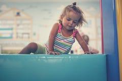 Bebê caucasiano pequeno no campo de jogos Escalada pequena feliz do bebê Fotos de Stock Royalty Free