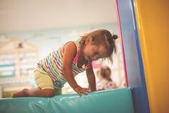 Bebê caucasiano pequeno no campo de jogos Escalada pequena feliz do bebê Fotografia de Stock Royalty Free