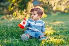 Bebê caucasiano que guarda a bandeira canadense com folha de bordo vermelha Fotografia de Stock
