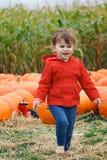 Bebê com as abóboras na exploração agrícola, Dia das Bruxas Fotografia de Stock Royalty Free