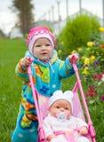 Bebê com a boneca na caminhada Fotos de Stock Royalty Free