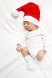 Bebê com chapéu de Santa Claus que dorme na cama imagem de stock royalty free