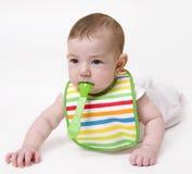 Bebê com a colher na boca que olha de lado imagem de stock