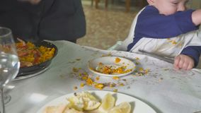 Bebê com a mãe que come o paella em um restaurante filme