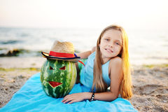 Bebê com a melancia que encontra-se na praia contra o mar Foto de Stock Royalty Free